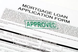 A paper with mortgage oan application form on the top in bold letters with a paragraph written underneath. There is a green stamp stating approved in capitalized letters (diagonally)
